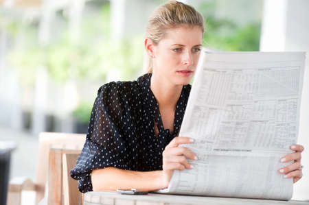 A young attractive woman reading newspapers at a cafeteria photo