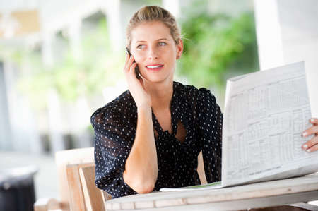 A young attractive caucasian woman talking on her phone while reading newspapers at a cafeteria Stock Photo