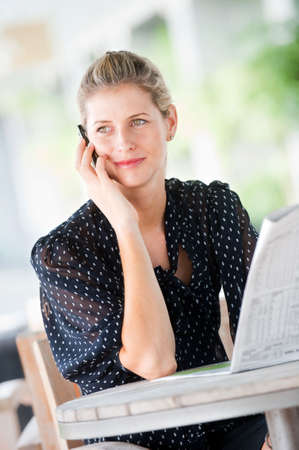 A young attractive caucasian woman talking on her phone while reading newspapers at a cafeteria Stock Photo - 6338233
