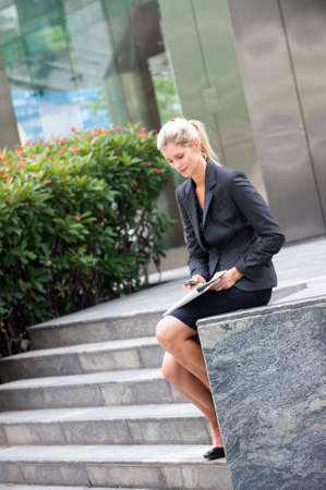 A young and attractive businesswoman using her phone in the city photo