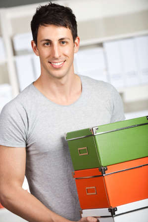 An attractive man carrying cardboard boxes at home photo