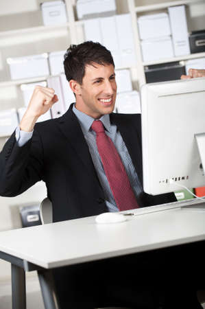news online: An attractive businessman receives good news online at his office
