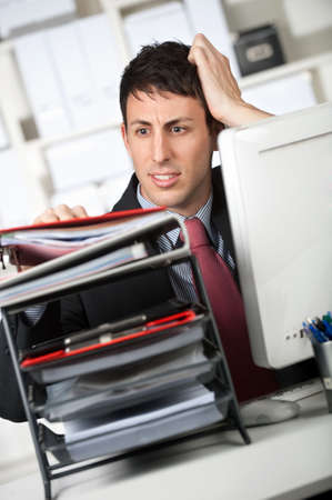 An attractive businessman with a heavy workload in the office photo