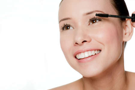 Beauty portrait of a young and attractive woman applying mascara isolated on white background Standard-Bild