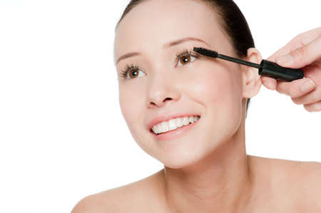 Beauty portrait of a young and attractive woman applying mascara isolated on white background Stock Photo