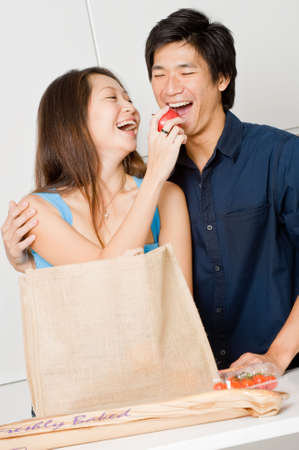 An attractive couple unpacking groceries in the kitchen at home photo