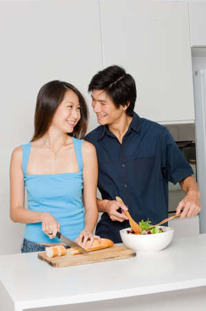 A good looking couple preparing a meal of bread and salad in the kitchen at home