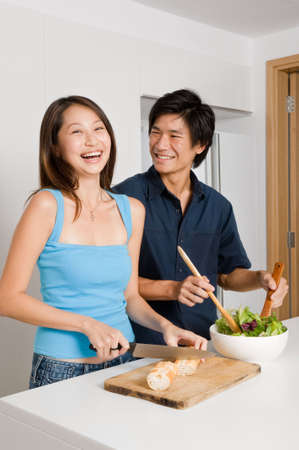 asian couple happy: A good looking couple preparing a meal of bread and salad in the kitchen at home