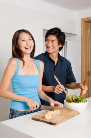 asian home: Un paio di buona ricerca preparando un pasto di pane e insalata in cucina a casa