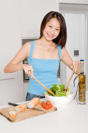 A good looking woman preparing a healthy meal of bread and salad in her kitchen at home photo