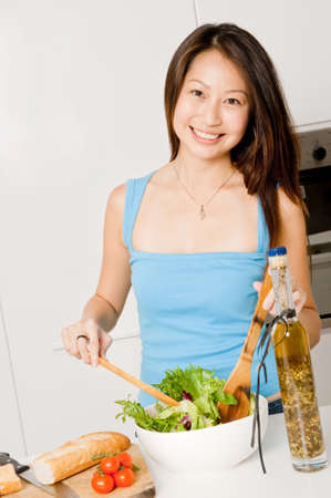 A good looking woman preparing a healthy meal of bread and salad in her kitchen at home