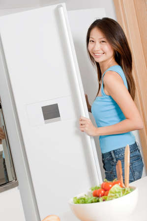 Eine gut aussehende Frau suchen in Ihr Kühlschrank bei der Vorbereitung ein Salat in Ihrer Küche