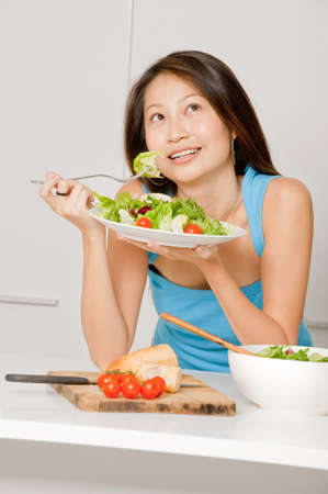 A good looking woman eating a healthy meal of bread and salad in her kitchen