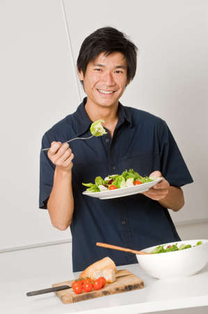 good looking man: A good looking man eating a healthy meal of bread and salad in his kitchen Stock Photo