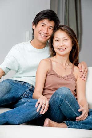 asian couple happy: A good looking couple relaxing on their couch at home