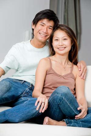 pareja en casa: Un par de buena pinta relajante en su sof� en casa