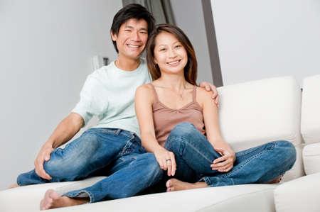 asian home: Un paio di buona ricerca rilassante sul loro divano a casa  Archivio Fotografico