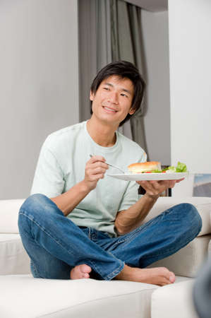 adult sandwich: A good looking man having a sandwich on his couch at home