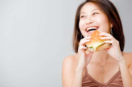Eine gut aussehende Frau, die mit einen Sandwich vor weißem Hintergrund
