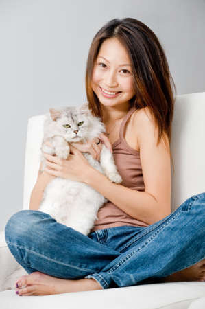 A good looking woman holding up her pet cat in her home