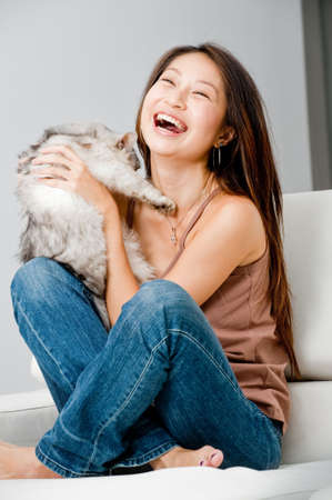 A good looking woman holding up her pet cat in her home photo