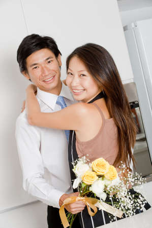 A good looking man giving a bouquet of flowers to his wife at home photo
