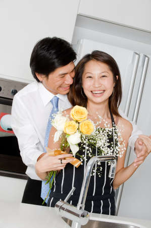A good looking man surprising his wife with a bouquet of flowers at home photo