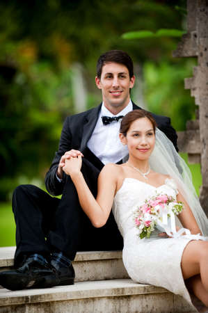 An attractive young bride and groom sitting on steps and holding hands outdoors photo