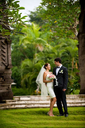 An attractive young bride and groom smiling at each other in a garden outdoors Stock Photo - 6593106