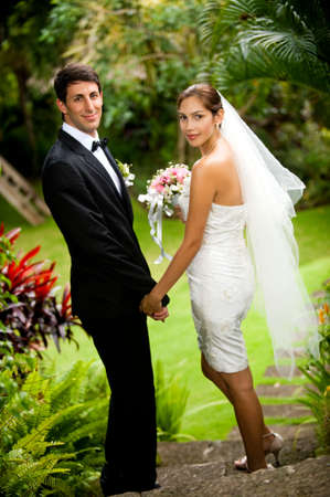 An attractive young bride and groom holding hands and walking down steps outdoors photo