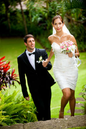An attractive young bride leading her groom up some stone steps outdoors photo