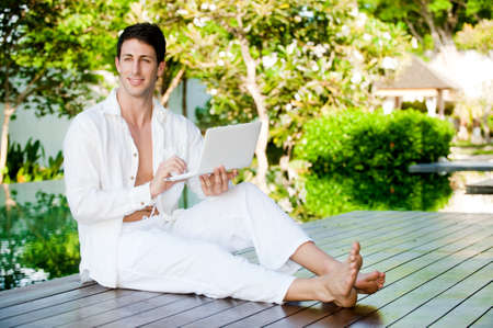 An attractive man lounging by the pool with his laptop outdoors photo