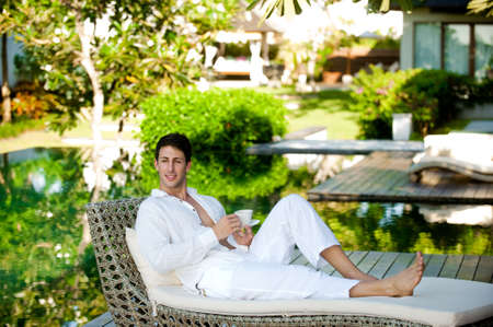 An attractive man lounging on a daybed with a drink outdoors photo