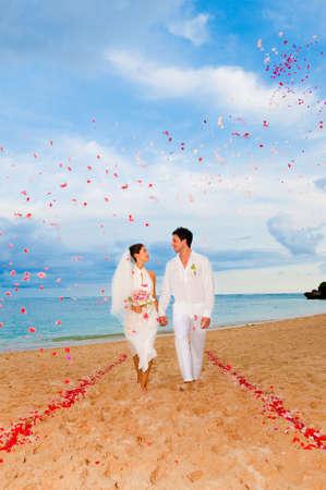 Eine attraktive Braut und Bräutigam heiraten am Strand
