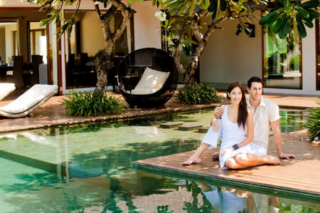 An attractive couple relaxing by the pool outdoors