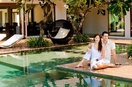 Ein attraktives Paar entspannenden durch von der Pool im freien  Lizenzfreie Bilder