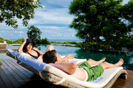 Ein attraktives junges Paar in Bademode entspannenden durch von der Pool im freien