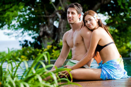 man resting: An attractive young couple in swimwear relaxing by the pool outdoors