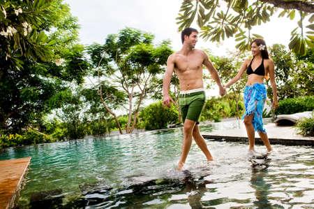 Ein attraktives junges Paar in Bademode, die zu Fuß durch einen Pool im freien