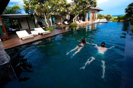 Eine attraktive junge paar Schwimmen in einem Pool im freien