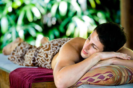 An attractive young man lying on a massage bed at a spa outdoors Stock Photo - 6672471