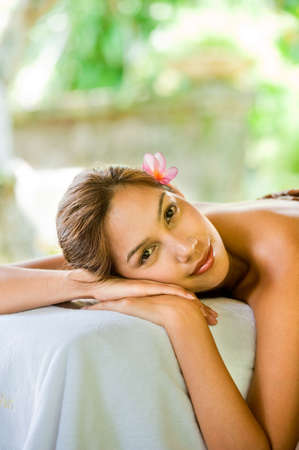 An attractive young woman lying on a massage bed at a spa outdoors photo
