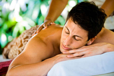 An attractive young man enjoying a back massage at a spa outdoors