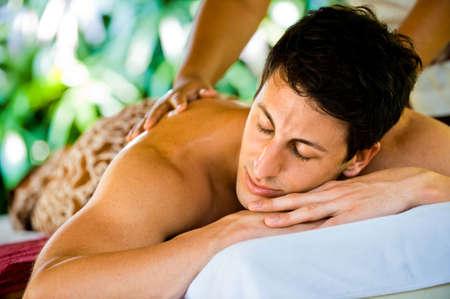 Eine attraktive junger Mann genießen eine Back Massage auf ein Spa im freien