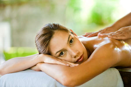 An attractive young woman enjoying a back massage at a spa outdoors
