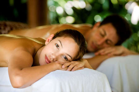 back massage: An attractive young couple lying on massage beds at a spa outdoors
