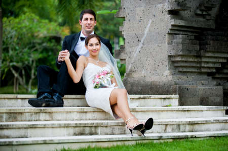 An attractive young bride and groom sitting on steps and holding hands outdoors Stock Photo - 6612155