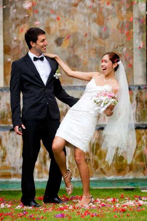 Eine attraktive junge Braut und Bräutigam am einem Wasserfall im freien