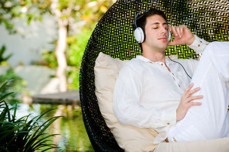 An attractive man listening to music and relaxing outdoors