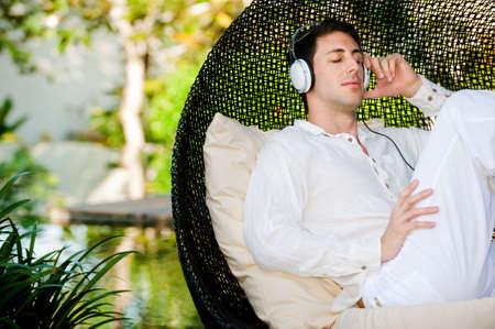 Ein attraktiver Mann Musik hören und Entspannen im freien